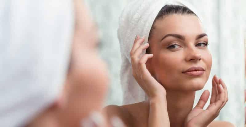 Junge Frau mit perfekter Haut vor dem Badezimmerspiegel