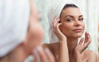 Frau im Badezimmer kontrolliert ihr aknefreies Gesicht