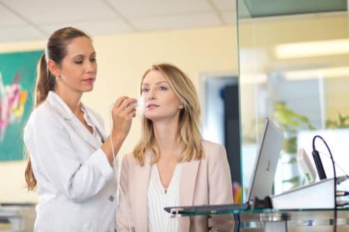Behandlung der Gesichtshaut einer Frau durch Dr. Bauer
